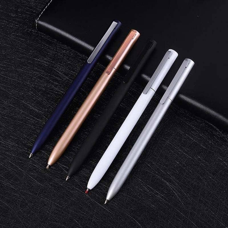 5 stylos à bille minces de couleurs différentes posés sur un carnet noir