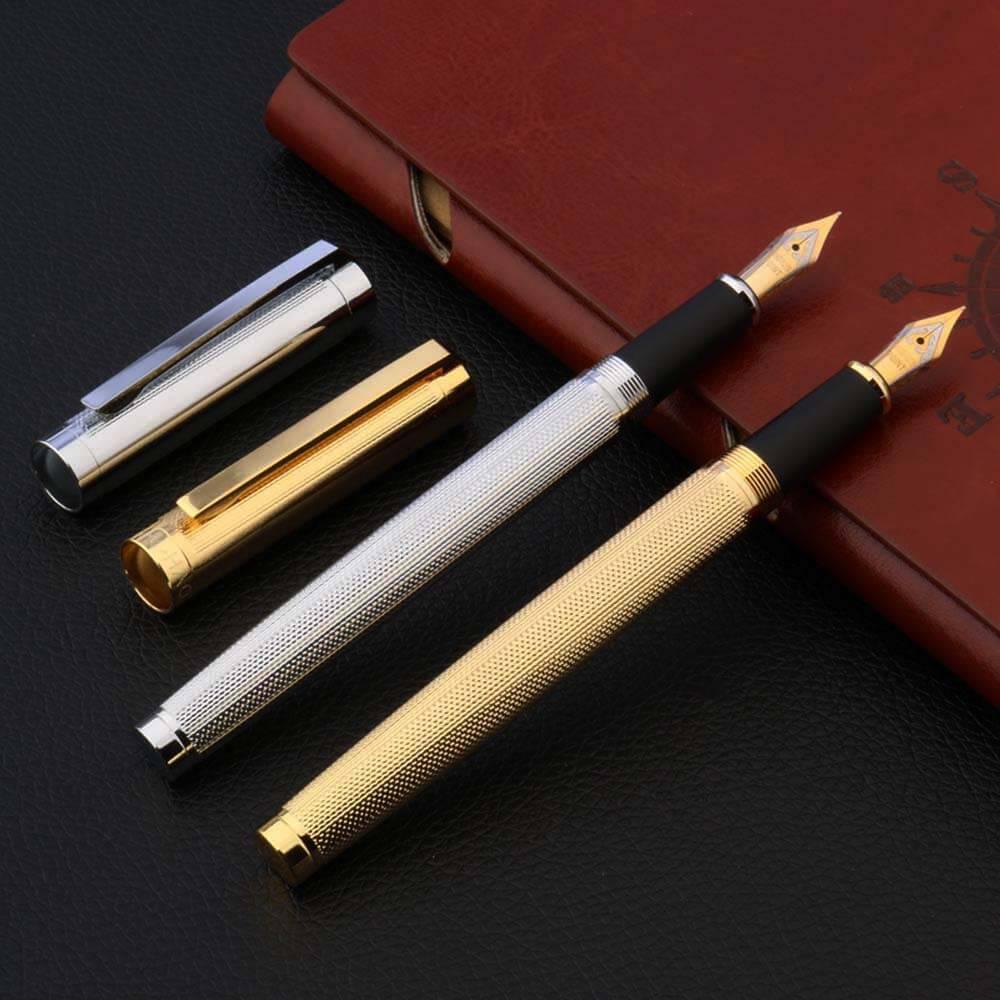 Stylo à plume piquant doré et argent posé sur un carnet brun et sur un support noir