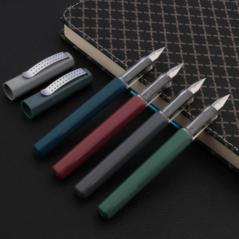 4 stylos plume colorés avec leur capuchon détaché sur un carnet noir
