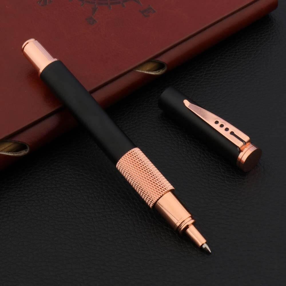 Stylo à bille piquant rose posé sur un carnet brun et un support noir